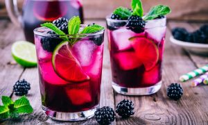 two ice cold glasses of blackberry lemonade